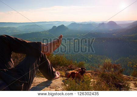 Naked Male Hairy Legs In Dark Hiking Trousers Take A Rest On Peak Of Rock Above Valley.