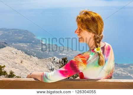 Middle aged caucasian woman sits view at sea and coastline