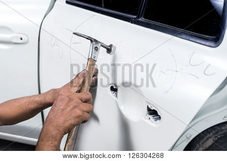Auto body repair series : Mechanic fixing dented car door