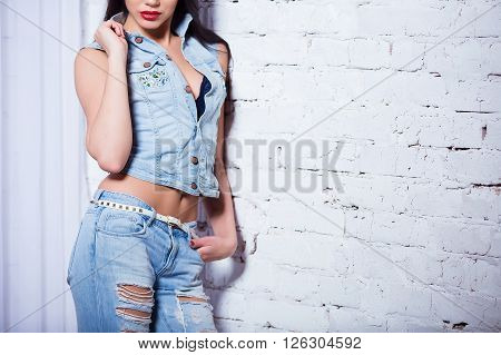 Closeup of sexy alluring woman belly. Slim girl with red lips wearing jeans . Hotness and sexiness