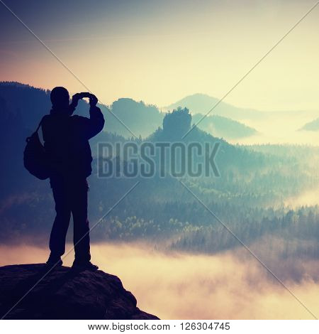 Tourist With Backpack Takes Photos With Smart Phone On Peak Of Rock. Dreamy Fogy Valley Below