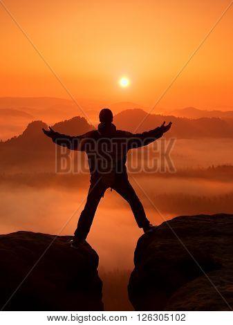Hiker In Black Celebrate Triumph Between Two Rocky Peaks. Wonderful Daybreak In Rocky Mountains, Hea