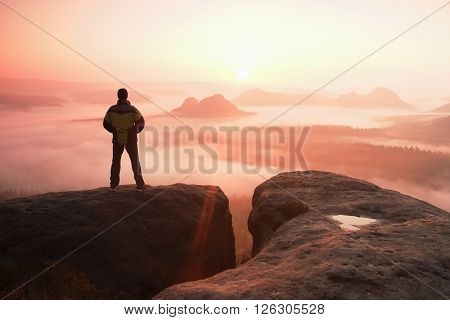 Moment of morning. Man on the rock empires and watch over the misty and foggy morning valley.