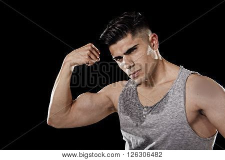 young attractive sport man with big and strong athletic body wearing sweaty singlet posing with arm bent showing bicep muscle in healthy fitness club and corporate gym concept isolated on black