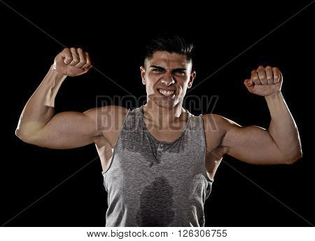 young attractive sport man with big and strong athletic body posing with arms bent showing bicep muscle chest and shoulders in healthy fitness club and corporate gym concept isolated on black