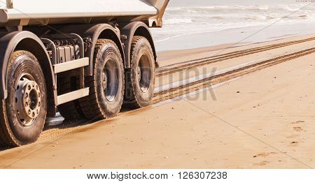 Truck races across the beach at high speed at the water's edge