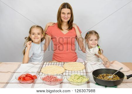 Mother With Two Daughters At The Kitchen Table Are Going To Cook A Pizza And A Fun Look Into The Fra