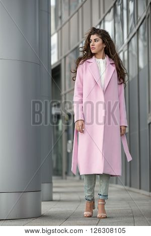 Stylish young girl with beautiful hair stands near the columns on the glass wall background. She wears pink coat with belt, white blouse, light jeans and beige sandals. She looks to the left. She has two rings on her right hand. Outdoors. Vertical.
