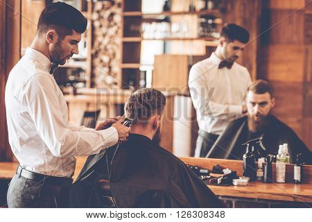 Nape trim. Rear view of young bearded man getting haircut by hairdresser with electric razor while sitting in chair at barbershop in front of mirror