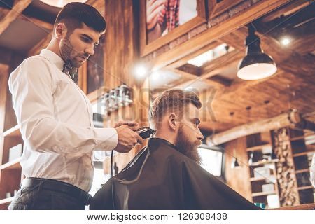 Perfect trim at barbershop. Low angle view of young bearded man getting haircut by hairdresser with electric razor while sitting in chair at barbershop