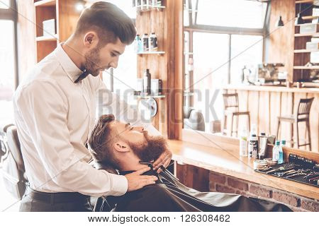 Making his beard stylish. Side view of young bearded man getting shaved with straight edge razor by hairdresser at barbershop