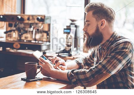 Technologies make life easier. Side view of young handsome man using his digital tablet while sitting at bar counter at cafe