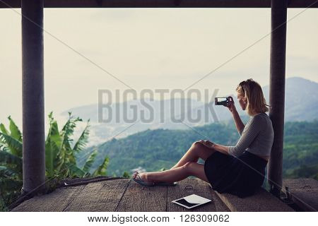 Young woman wanderer is shooting video on her mobile phone while is sitting against subtropical landscape and sky background with copy space for your advertising text message or promotional content