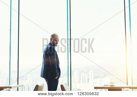 Young man successful lawyer is waiting for his client to discuss certain issues before the court session while is standing near window with copy space background for your advertising text message
