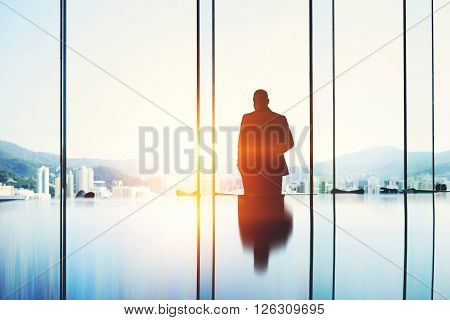Silhouette of a man entrepreneur is pondering over the idea a business partnership which he got during a trip to China while is standing in modern skyscraper interior against window with copy space