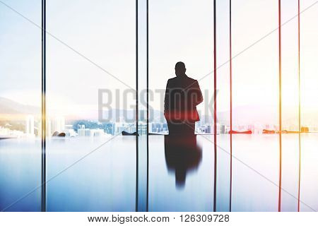 Silhouette of a man successful lawyer is thinking about the future of an important court session while is standing in modern office interior near big window with view of developed Hong Kong city