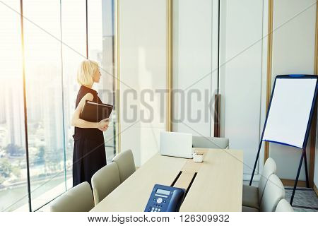 Woman skilled manager is reading presentation that she wrote for investors on flip chart with copy space for your advertising text message or promotional content while is standing in conference room