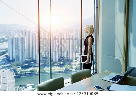 Young successful businesswoman with digital tablet in hand is thinking about future of her construction company while is standing in modern office interior near window with Cityscape view. Copy space