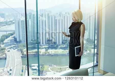 Young beautiful businesswoman dressed in elegant black dress with digital tablet in hand is reading e-mail on cell telephone while is standing near office window with view of developed Hong Kong city