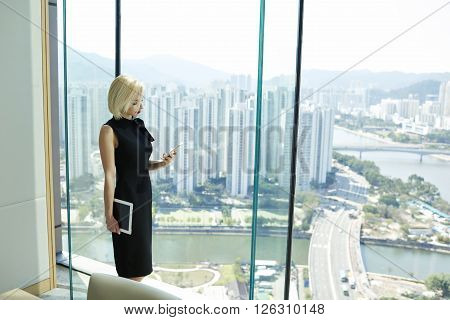 Young woman successful economist of big trading real estate company is checking e-mail on cell telephone standing near skyscraper office window with view of metropolitan city with good infrastructure