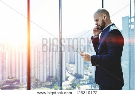 Furious man professional banker is read in internet via touch pad information about a sharp drop in currency at the market. Businessman is standing in office interior near window with copy space area