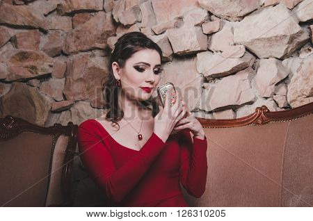 Pensive woman in red dress holding a mirror, thoughtfully looks at her face with bright makeup smoky eyes, red lips, hairstyle. Elegant portrait brunette 30 year old female in classic interior.