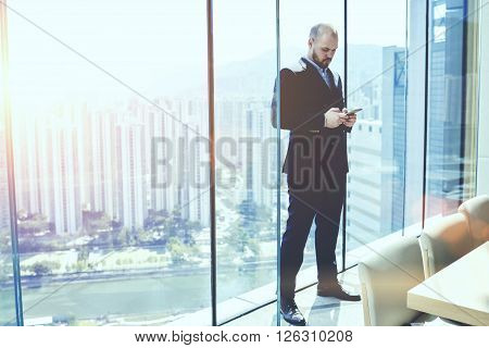 Young serious man CEO in suit is ordering o-nline car for business trip via cell telephone while is standing in conference room against window with view of Hong Kong city background with copy space