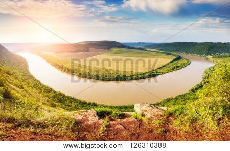 Sinuous river flowing through the canyon in the sunlight. Dramatic and picturesque scene. Location place Dnister. Ukraine, Europe. Beauty world.