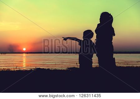 Silhouette of parent and child enjoying the view at riverside. Colorful sunset sky background. Boy pointing to empty copy space at sky. Friendly family. Cross process. Vintage style.