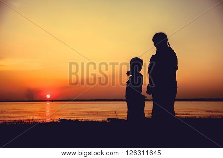 Silhouette of mother and child enjoying the view at riverside. Boy pointing to empty copy space at sky. Colorful sunset sky background. Friendly family.