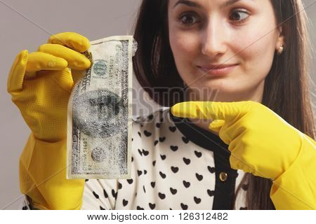 woman pointing to the wet money (illegal cash dollars bill corruption manipulation)