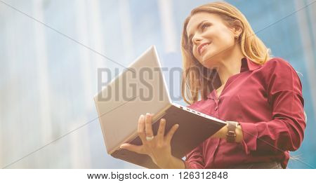Businesswoman working with laptop computer in the city centre. Pretty lady in vivaceous blouse waiting for her partners.