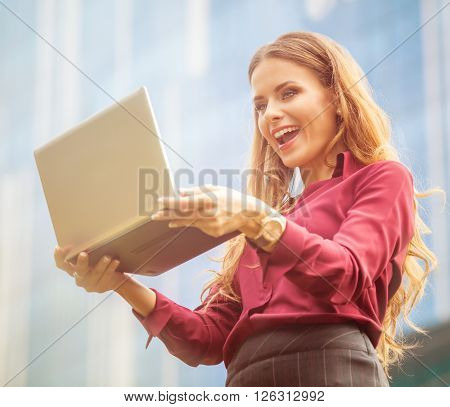 Businesswoman smiling for the camera in laptop in front of officebuilding. Lady communicating with her partners using Skype. She is smiling.