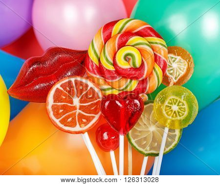 bright multicolored lollipops on the background of colorful balloons. Lollipops in the foreground closeup