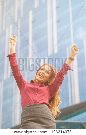 Businesswoman in vivaceous blouse and grey skirt celebrating victory in the city. Lady raised hands, she is happy smiling isolated on office building background.