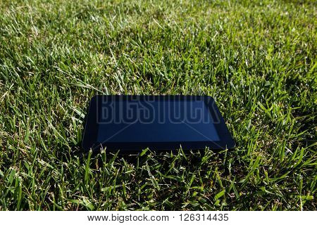 black tablet pc over green grass background
