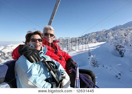 Hombre Senior y senior mujer sentada en un telesilla