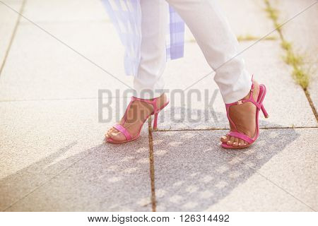 Close-up picture of woman's legs in pink heels. White trousers and pink heels are nic idea to have a walk in the city centre. Toned image.