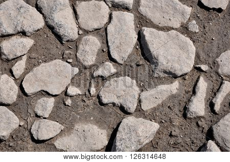 The texture of the stones and wet earth. Stones in the drying puddle
