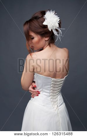 Elegant bride with brown short hair updo and bare shoulders white wedding dress view from the back