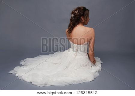Bridal fashion. Brunette bride with pearl headpiece and white wedding gown view from the back sitting in a pile of tulle fabric.