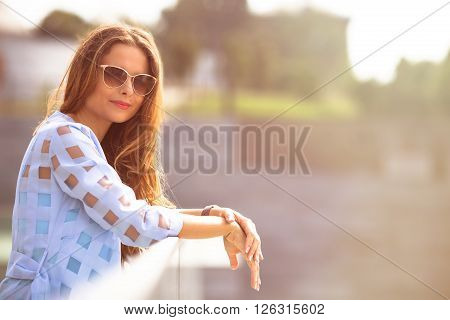 Attractive lady in sunglasses standing on the bridge and looking at the camera. Pretty lady spending her weekends outside. Toned image.