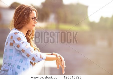 Happy middle-aged woman enjoying warm summer day. Lady in sunglasses standing on the bridge and looking at the river. Toned image.
