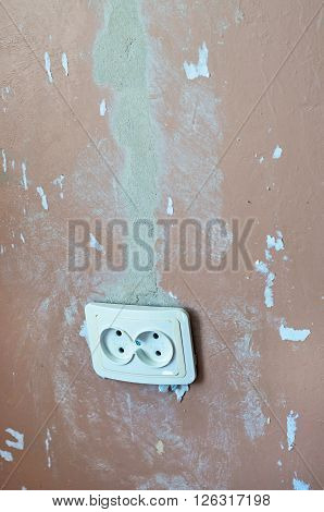 electrical outlet on the wall with the paper remains