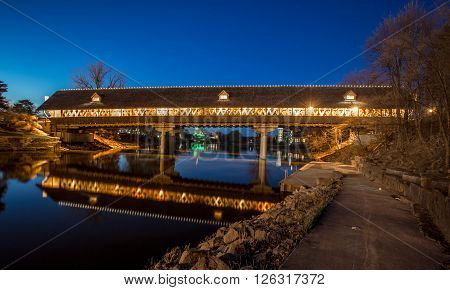 Frankenmuth Covered Bridge At Night. Frankenmuth wooden bridge illuminated at night with the city skyline in the background. Frankenmuth, Michigan.