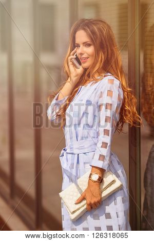 Pretty caucasian businesswoman talking on cell phone by office building. Smiling lady with long brown hair waiting for her collegues. Toned image.