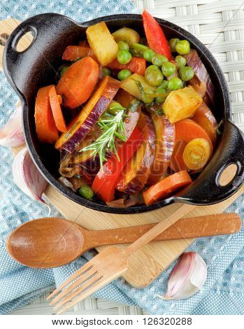 Delicious Homemade Colorful Vegetables Ragout with Eggplant Carrots Potatoes Leek Red Bell Pepper and Green Pea in Black Iron Stewpot with Wooden Spoon and Fork closeup on Blue Napkin