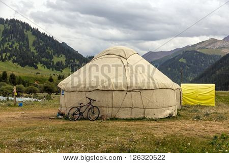 Traditional Mongol Nomad Housing assembled on Green Meadow among High Mountain Hills in Kyrgyzstan and a Bicycle lean on it
