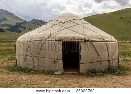 Traditional Mongol Nomad Housing assembled on Green Meadow among High Mountain Hills in Kyrgyzstan with Opened Entrance door and Yellow Steppe Grass on foreground