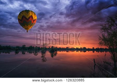 multicolored balloon at sunset over the lake